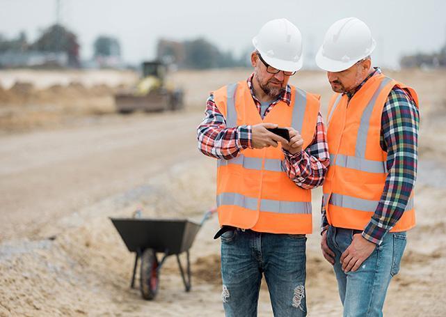 mężczyźni wkamizelkach odblaskowych ihełmach patrząca wtelefon